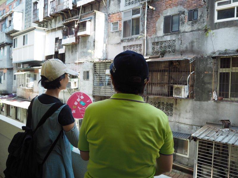 由於北市現兩處公辦都更案未來都將有部分住宅做為公共住宅使用,斯文里長江雪卿(左)帶著20多名報名民眾走入斯文里三期整宅。(尹俞歡攝)