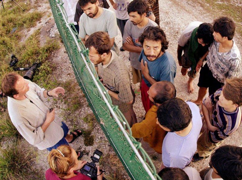 一名西方記者正試圖穿越鐵絲圍欄,以採訪拘留營內被隔離的難民。(美聯社)