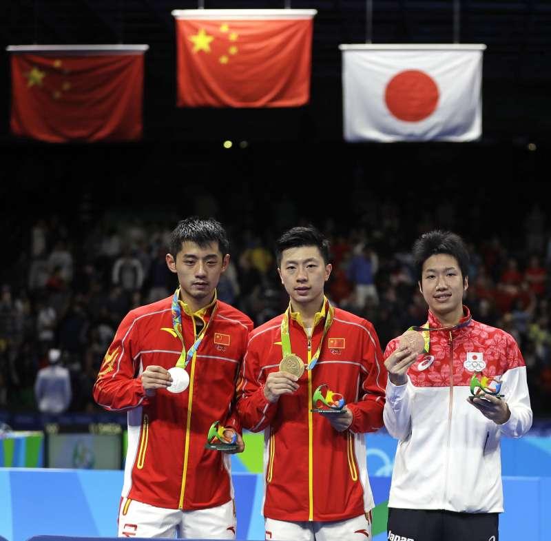 桌球男子單打金牌馬龍(中)、銀牌張繼科(左)、銅牌水谷隼(右)。(美聯社)