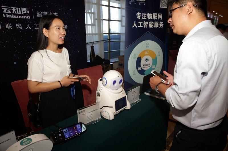 中國人工智慧大會在北京開幕,一名參展工作人員介紹「小優機器人」,它可以識別語音,主要應用於陪伴兒童。 (新華社)