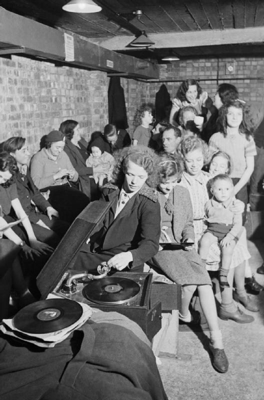 倫敦民眾帶著家當躲在防空洞內,一名女子在防空洞內播起音樂。(維基百科/public domain)
