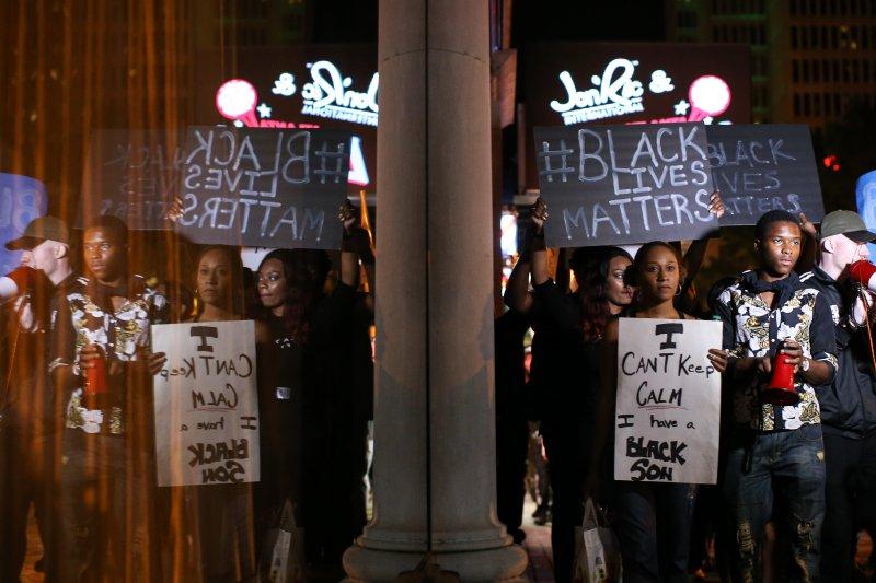 抗議警方濫殺黑人的民眾群聚街頭,高舉「黑人的命也是命」標語。(美聯社)
