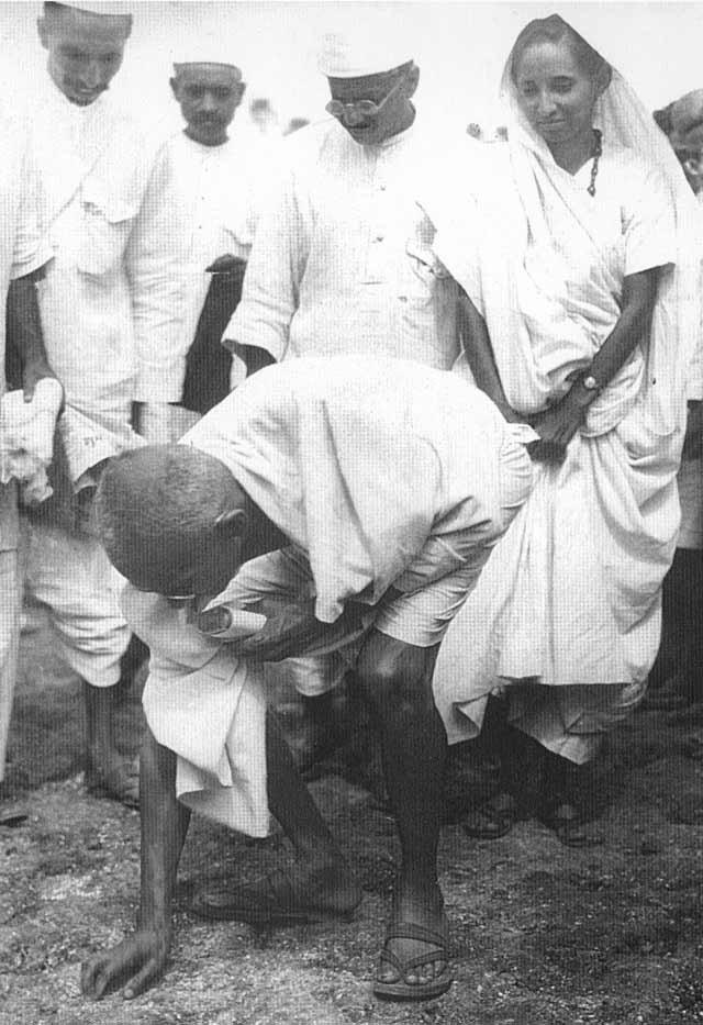 甘地拾起一把海鹽,並對群眾喊話。(wikipedia/public domain)