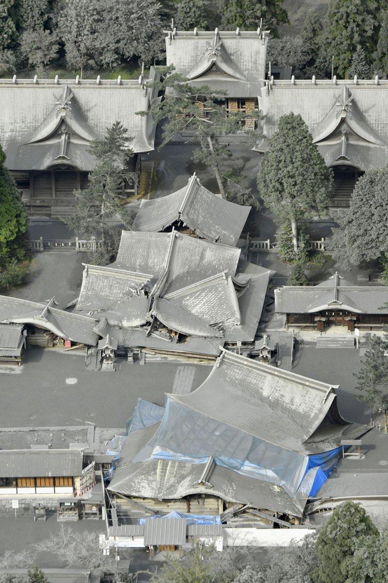 因為地震傾倒的阿蘇神社,8日因為阿蘇火山爆發,又蒙上一層火山灰。(美聯社)
