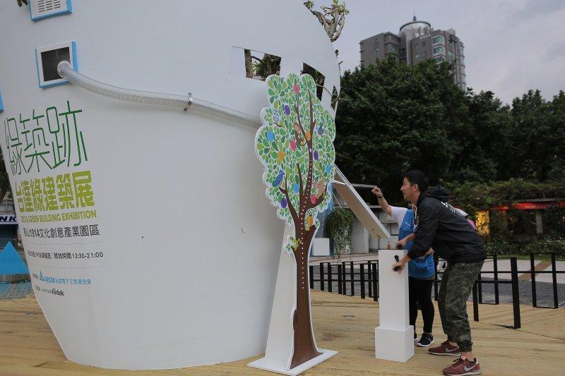 參觀民眾奮力地轉動發電把手,一旁台達基金會解說員透過扭蛋中的種子及摺紙,傳達氣候變遷的應對之道。(圖/台達電子提供)