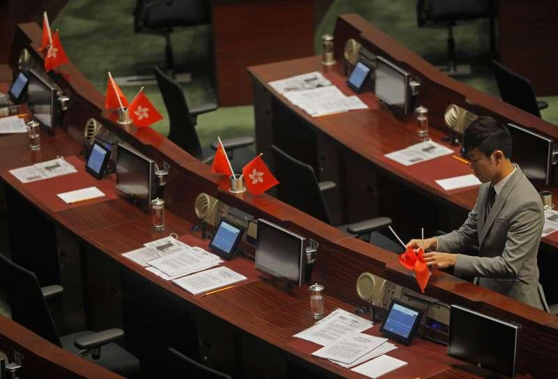 香港立法會議員鄭松泰把建制派議員放在桌上的中國國旗及香港旗幟上下倒轉擺放。(美聯社)