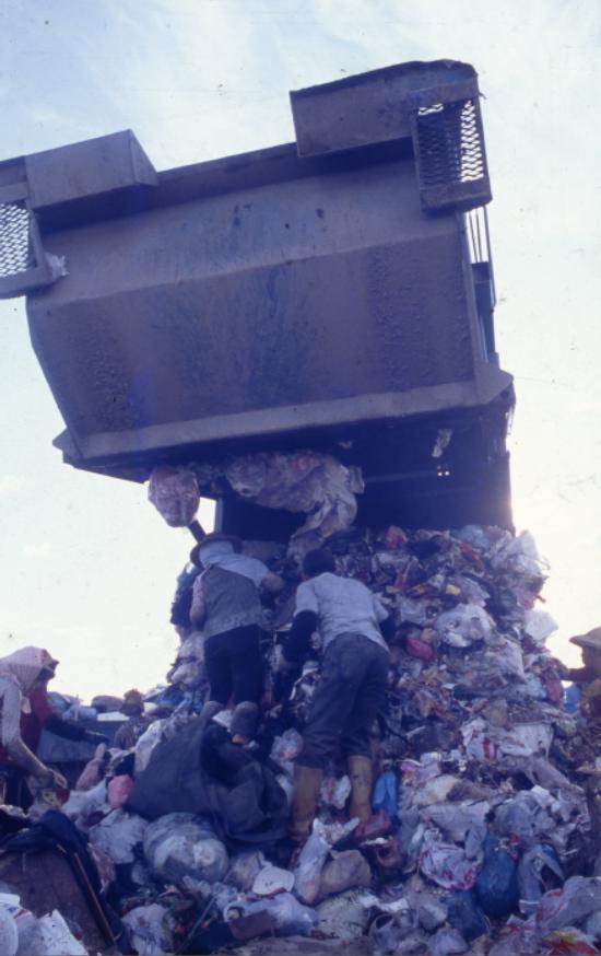 垃圾車的閘門開啟,拾荒者蜂擁而上,撿拾有市場價值的廢棄物。(蔡明德攝,南方家園提供)
