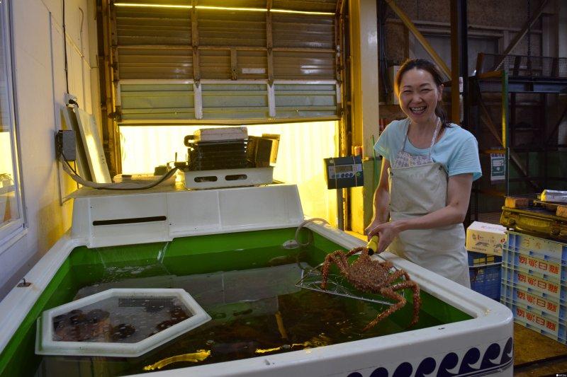 老闆娘正拿著當天捕獲的三公斤鱈場蟹,可以在立刻在工場現煮現吃。(圖/MATCHA提供)