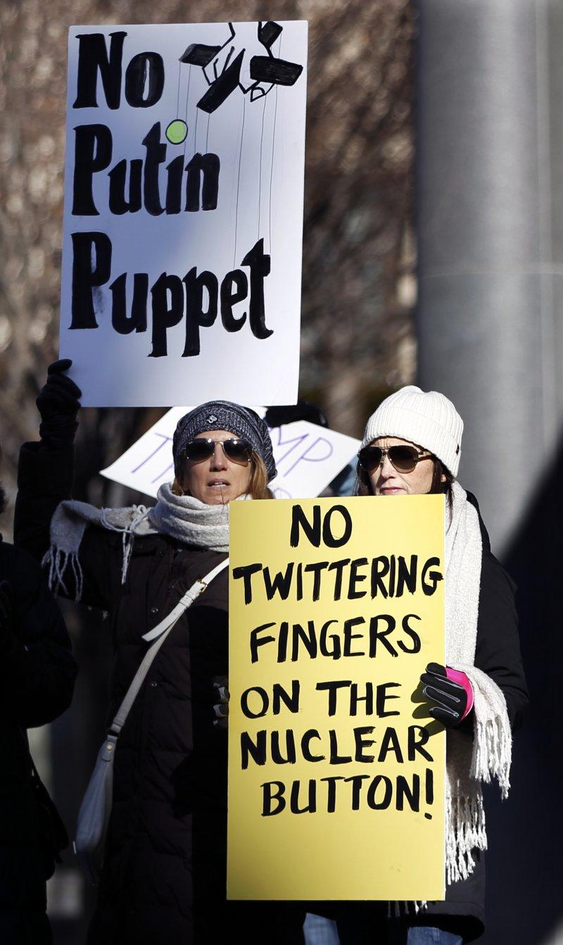 抗議川普的民眾舉著「不要普京的魁儡」、「不要讓發推特的手靠近核彈按鈕」諷刺川普一被激怒就發推特。(美聯社)