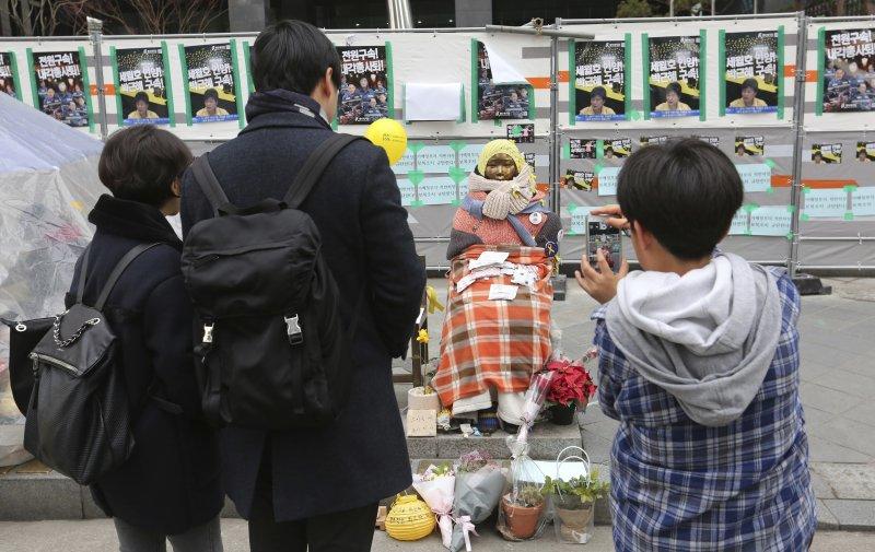 南韓民眾在日本駐南韓大使館外的慰安婦少女像旁拍照留念。(美聯社)