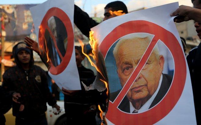 巴勒斯坦人恨夏隆入骨,聞其死訊後焚燒他的肖像。(美聯社)