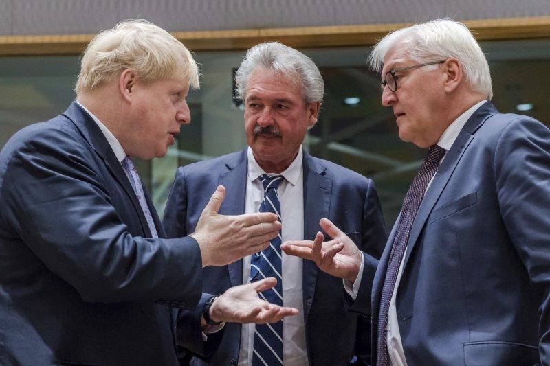 英國外長強森(左)與史泰因邁爾(右)、盧森堡外長阿森堡在16日的歐盟會議上談話。(美聯社)