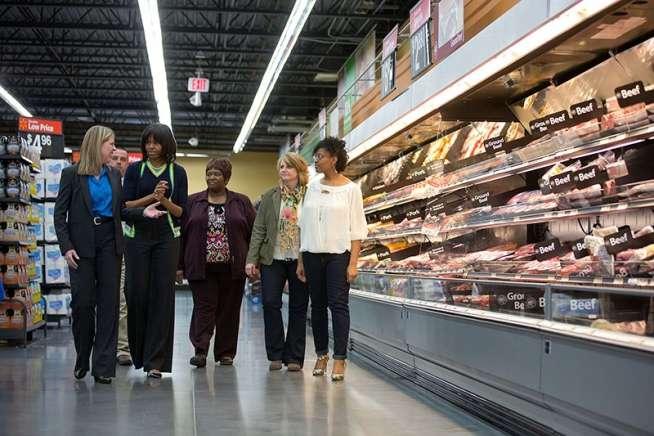蜜雪兒與美國連鎖超市沃爾瑪的副總和民眾一同逛超市,同時教導民眾如何選購健康食物,並建議超市提供更多價格合理的健康食物。(取自白宮)