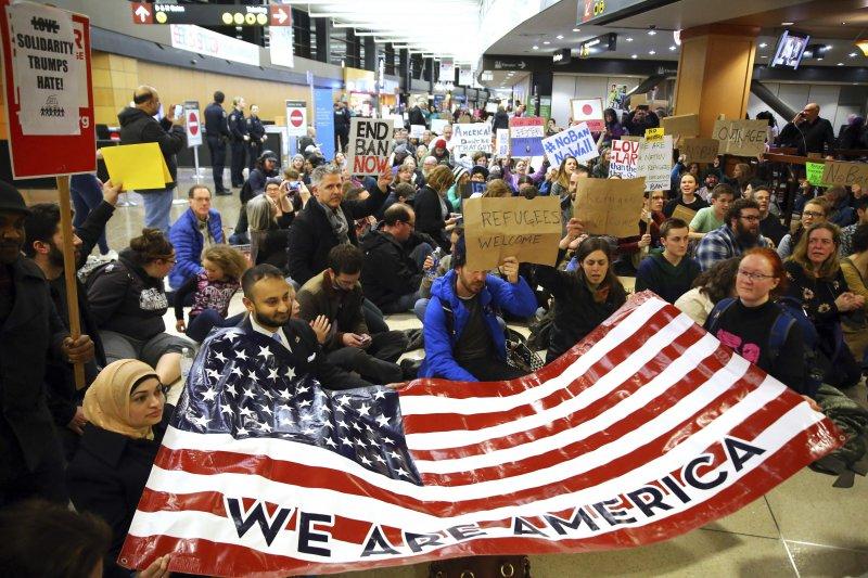民眾聚集在機場外抗議川普禁令。(美聯社)
