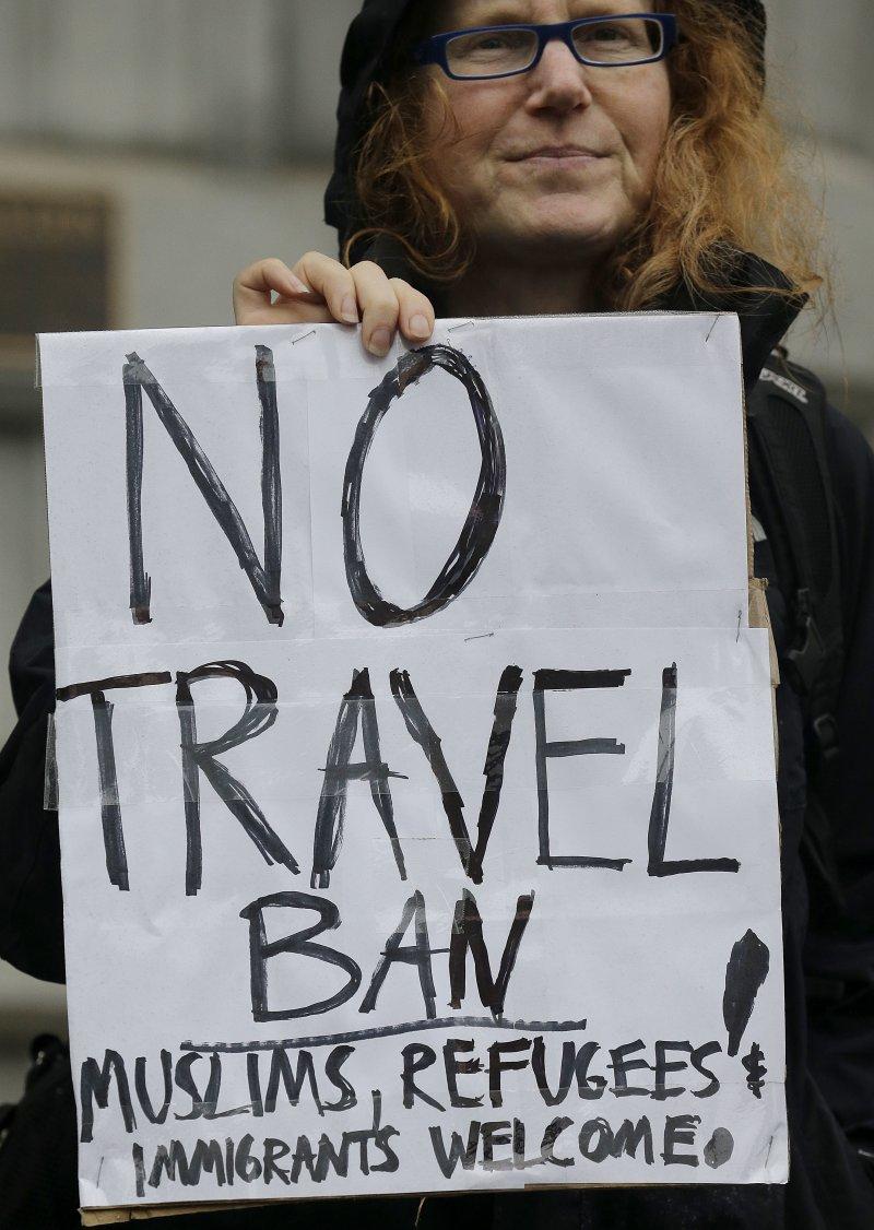 抗議川普的移民禁令民眾,拿著「沒有禁令,歡迎穆斯林、難民和移民」。(美聯社)