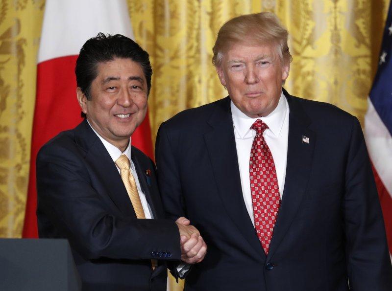 美國總統川普與日本首相安倍在記者會上握手。(AP)