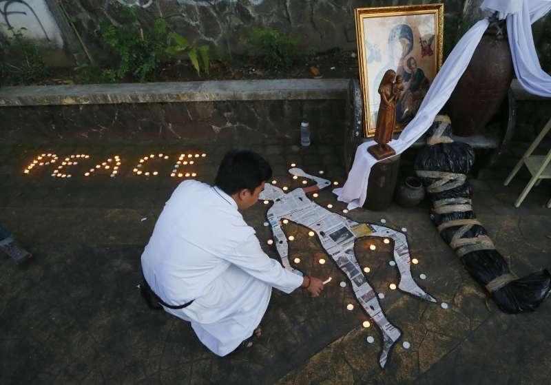 菲國天主教會神父在教堂外點起蠟燭,反對杜特蒂的血腥掃毒。(美聯社)