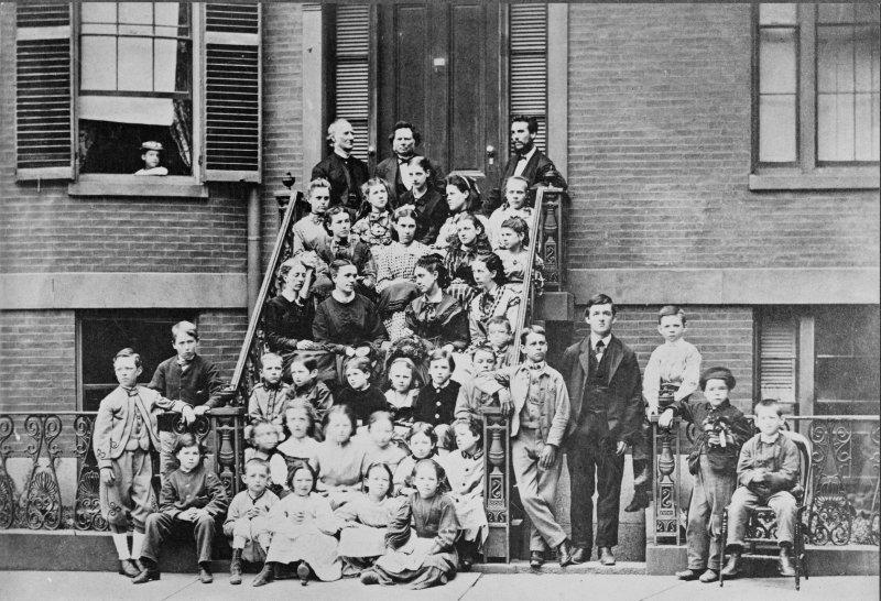 貝爾(最上方右邊)一生致力於聾人的口語教學,圖為他與學生合照。(圖/維基百科公有領域)