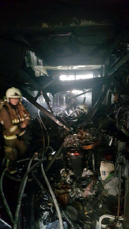 火勢控制後,消防隊員還要把一樓燒毀機車殘骸清出來。(圖/張毅攝)