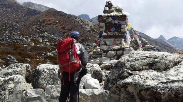 出事前的李小石向波蘭登山家捷西·庫庫奇卡(Jerzy Kukuczka)紀念碑鞠躬。(BBC中文網)