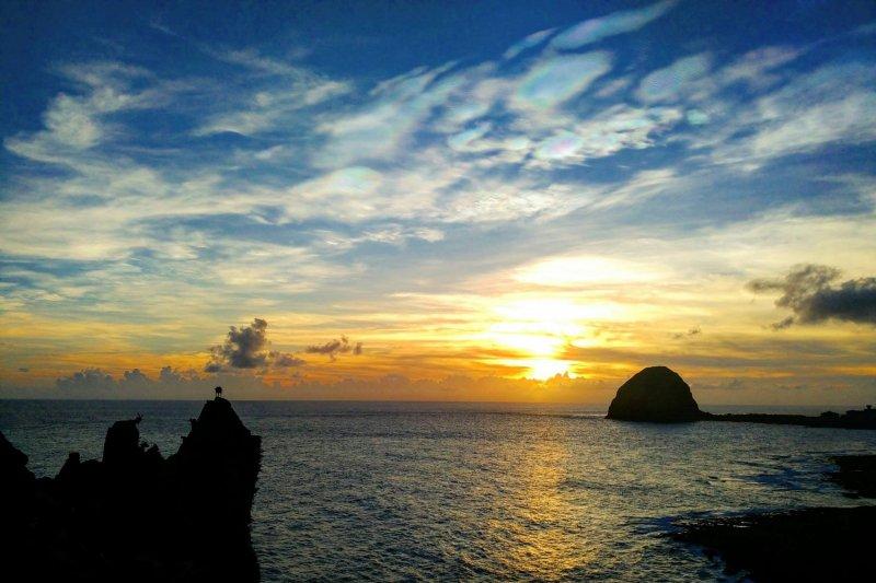 從虎頭坡欣賞日落,可以看到太陽從饅頭岩一旁緩緩落下海平面。(圖/俞嘉琦 拍攝)