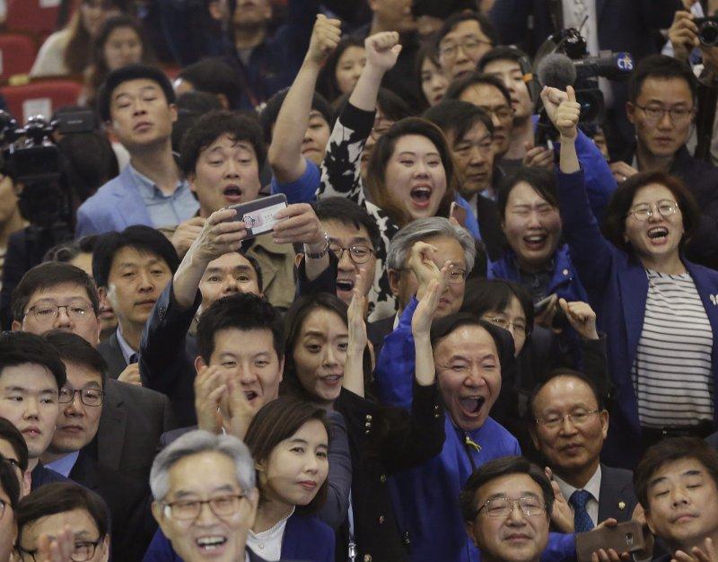 南韓大選出口民調已宣布,文在寅以41.4%遙遙領先,支持者歡呼。(美聯社)