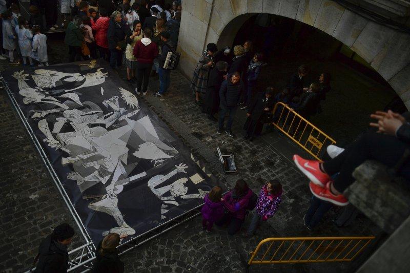 西班牙民眾圍繞著畢卡索的名畫「格爾尼卡」,哀悼西班牙內戰中的慘烈戰役。(美聯社)