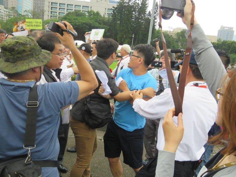 台北市同意遠雄移樹,松菸護樹志工團14日到國父紀念館向參加法鼓山活動的台北市長柯文哲抗議,穿藍衣者為游藝(松菸護樹)