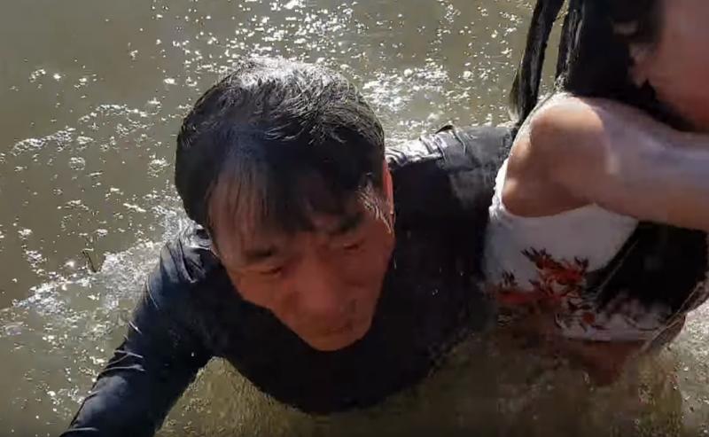 小女孩的祖父毫不遲疑,立刻跳下水搶救。(截自Youtube)