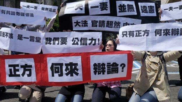 反對同婚人士3月24日憲法法庭開庭日在司法院外舉標語抗議。(BBC中文網)