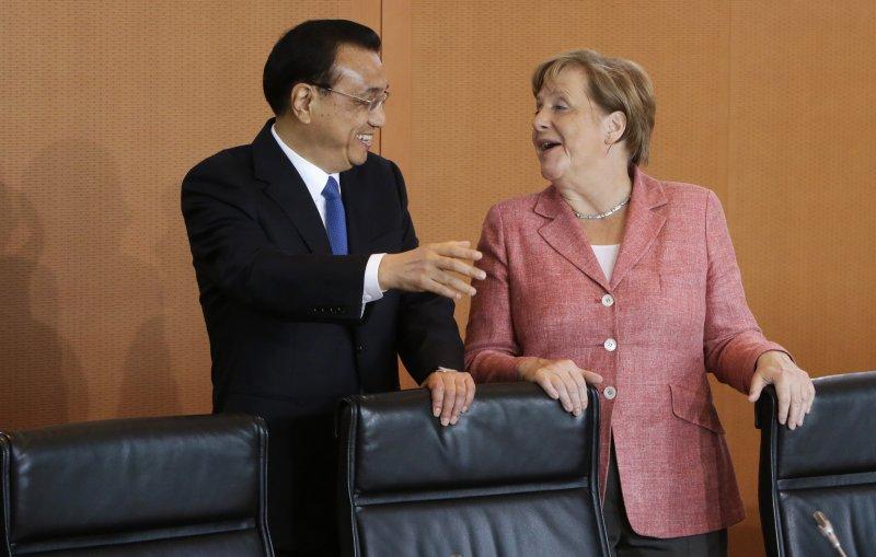 中國國務院總理李克強與德國總理梅克爾見面,中國也將宣布全力支持《巴黎氣候協定》。(美聯社)