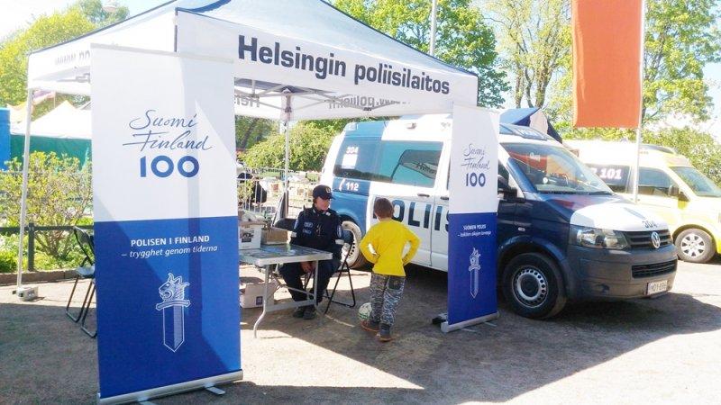 赫爾辛基市在每年5月最後一個週末舉辦「世界村園遊會」,參展單位之一赫爾辛基市警察局以「芬蘭100年」掛幅布置攤位。(圖片來源:作者攝影)
