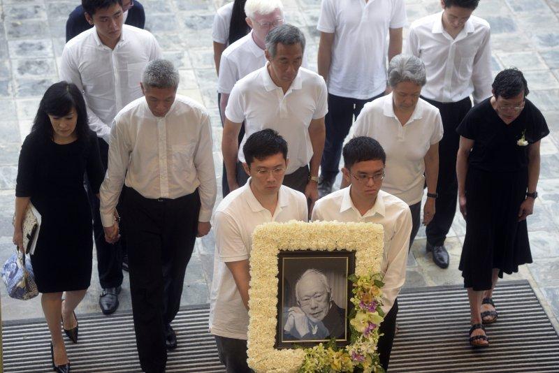 李光耀出殯時,他的子女緊緊跟在遺照後方:李顯龍(第二排中)、李顯揚(第二排左二)、李瑋玲(第二排右一)。(美聯社)
