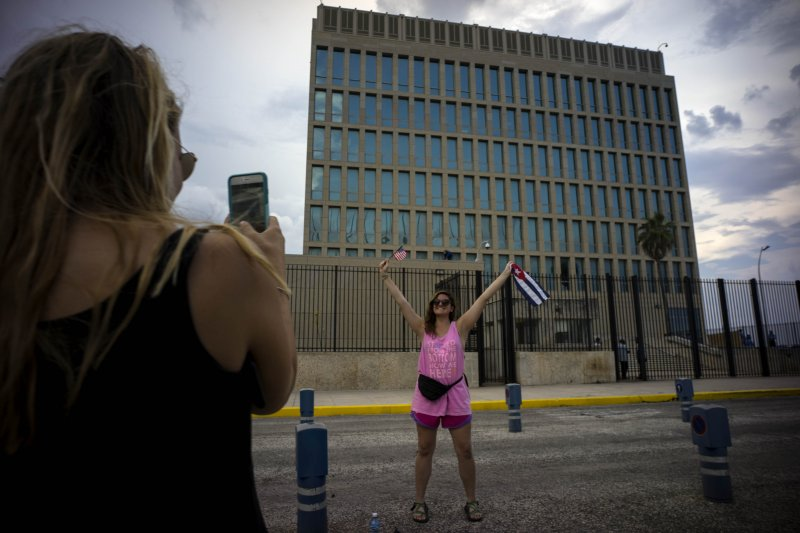 一名美國旅客在古巴留影,開心揮動古巴國旗。(美聯社)