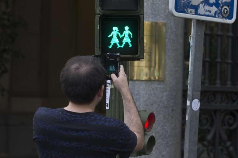 馬德里為了同志嘉年華活動,將原本小綠人紅綠燈號誌,換成綁馬尾或是穿裙子的女性小綠人或是同志手牽手的圖案。(美聯社)