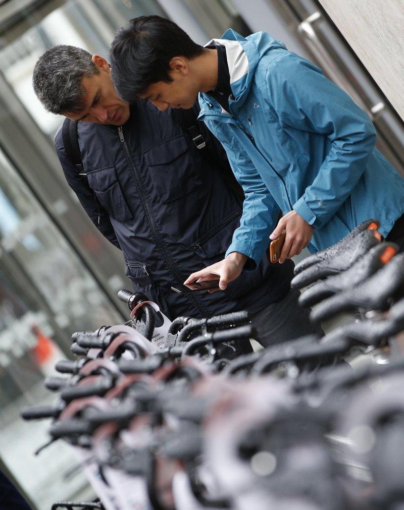 在英國曼徹斯特,市民準備體驗來自中國的摩拜單車。這是摩拜進軍歐洲市場的第一站,也是其在全球投放共用單車的第100個城市。(新華社)