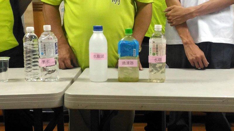 議員、里長拿出民眾家裡裝的水,的確偏黃且混濁。(圖/張毅攝)
