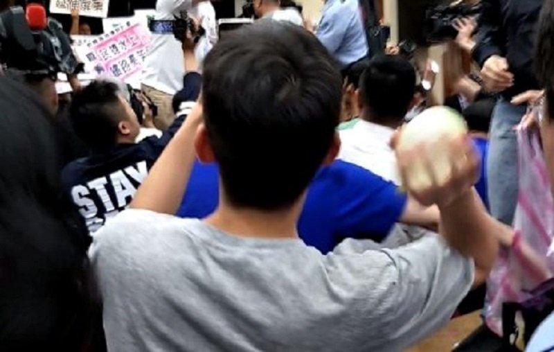 在媒體實習的韓姓學生「一時忘情」竟跟著拿起水球加入立委混戰。(周怡孜攝)