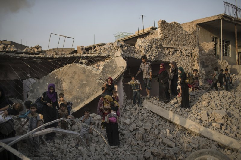 伊拉克軍隊7月初收復IS大本營摩蘇爾,圖為逃離交戰的當地女性。(美聯社)