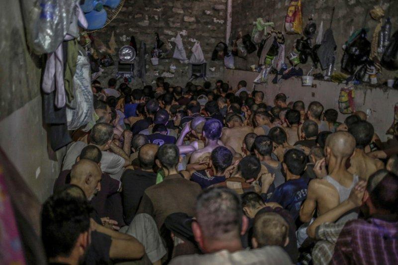 眾多被捕的IS成員擠在伊拉克臨時看守所內。(美聯社)