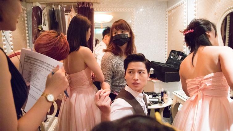 女同志Janerson(中間回頭者)婚禮前在化妝間和工作人員確認流程細節,在粉紅禮服的伴娘群中更顯英挺。(圖/曾千倚攝,親子天下提供)