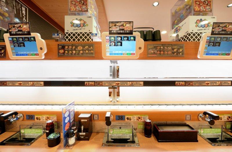 藏壽司在每個座位上都設置了扭蛋機,只要顧客在座位旁的回收槽裡,投入5個空盤,就能玩遊戲、抽扭蛋。(圖/藏壽司提供)