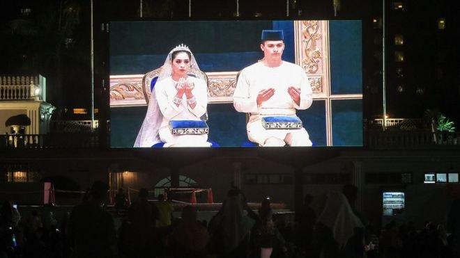 AFP 根據法新社的報道,婚禮上舉行了正式的「端坐」儀式,有約1200名公眾人士參加。城市廣場(Dataran Bandaraya)的人群在螢幕上觀看皇室婚禮。(BBC中文網)