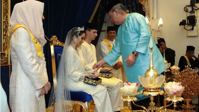 阿米娜是柔佛州蘇丹依布拉欣·依斯邁(Sultan Ibrahim Ismail ibni Sultan Iskandar)唯一的女兒(她排行第二,有五名兄弟)。家族成員及賓客向灑上有香味的水及黃米,表達祝福及認同。(BBC中文網)