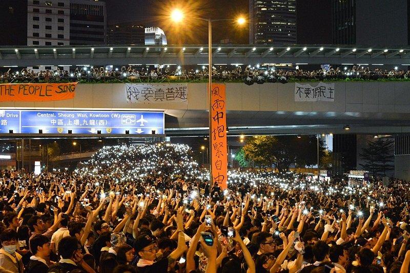 警方採取武力驅散後,數以萬計市民佔領金鐘主幹道,並亮起手機燈光。人潮經後方夏慤道天橋延伸至干諾道中。(維基百科)