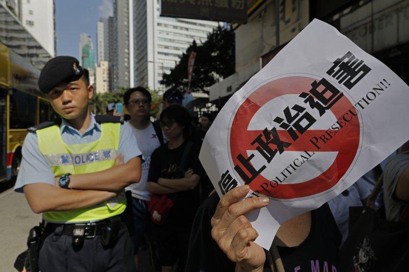 大批香港民眾20日上街遊行,,高喊釋放政治犯、良心犯等口號,聲援遭判刑入獄的青年世代政治領袖黃之鋒、羅冠聰與周永康(AP)