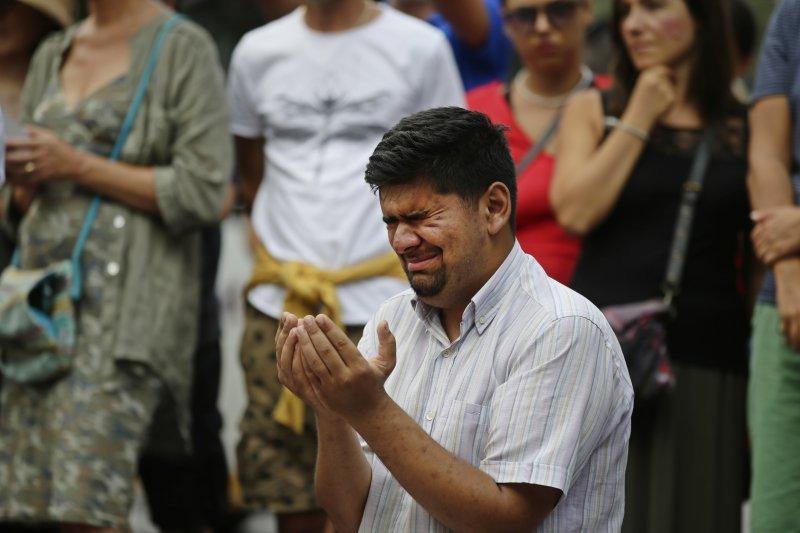 巴塞隆納恐攻案造成15人死亡、130人受傷,受害者家屬在現場悼念痛哭。(美聯社)
