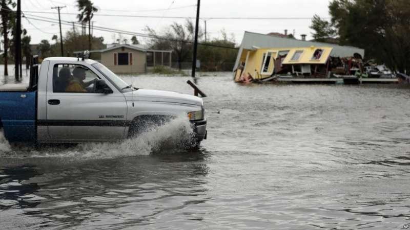德州受颶風哈維侵襲,一輛卡車在積水中駛過一幢受損嚴重的房子。(美國之音)