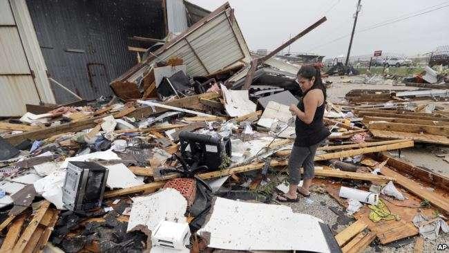 颶風哈維過後,德州凱迪一名婦女查看房屋受損情況。(美國之音)
