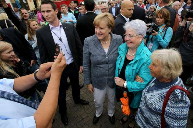 德國總理梅克爾(中)與支持者合照(AP)